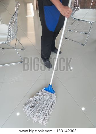 Maid Is Cleaning The Floor With Mop