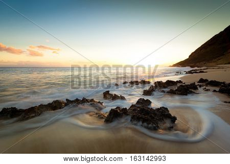 Ocean waves and rocks mingle at twilight on a secluded beach.