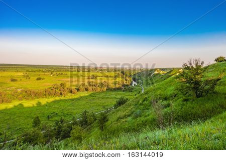 View of green ridge of chalk hills and flat plain with river.