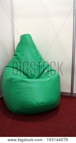 Bean bag made of green material is on the red carpet in a white wall