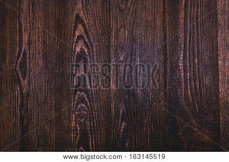 Dark brown wooden background. Texture. Top view.