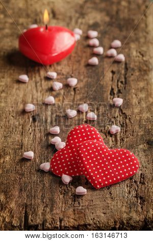 Two red hearts with heart shaped candies and candle on wooden background, valentine's day concept