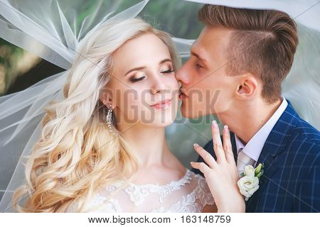 Wedding .Bride and Groom, Kissing at a Beautiful park on the wedding day., Romantic Married Couple .Wedding couple outdoors is hugging each other. Beautiful model girl in white dress. Man in suit.