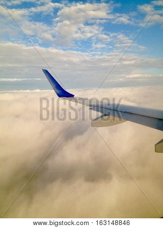 Airplane wing as plane flies above puffy white clouds