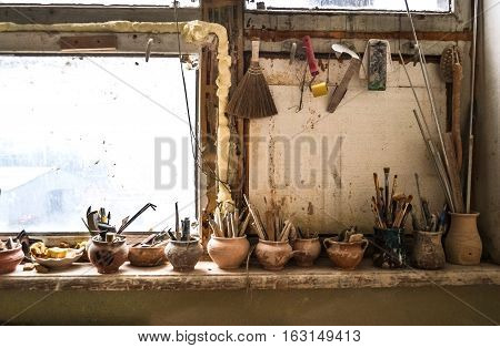 windowsill on which stand in vases tools in pottery