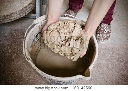 White clay soak in water. A girl holds a large white abstract piece of clay over a bucket after soaking. Preparation of white clay to work