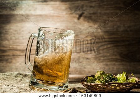 Beer spills from cup on wooden table next to hop in basket