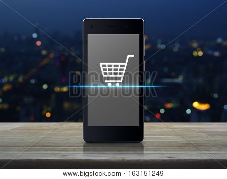 Shopping cart Icon on modern smart phone screen on wooden table over blur light city tower Shop online concept