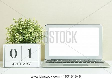 White wooden calendar with black 1 january word with white blank space at center of computer notebook on white wood desk and cream wallpaper textured background selective focus at the calendar