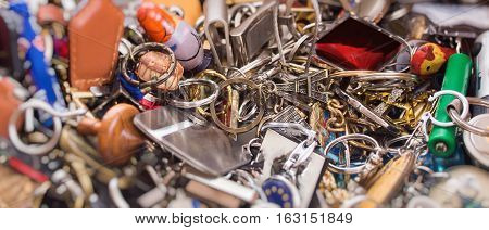 Many various colorful keychains in a box as a background