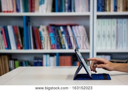 The Man Working On A Tablet Computer In The Library With The Books In The Background While Attemptin
