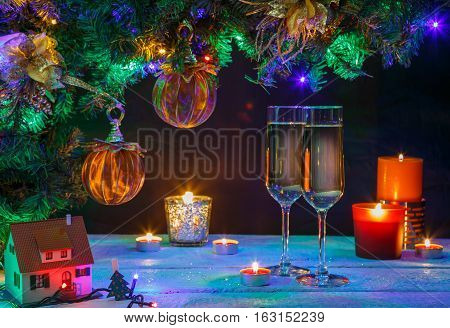 Two champagne glasses with candles and christmas tree. Christmas background.
