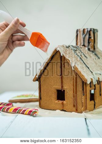 Glazing on homemade gingerbread house. Preparing for Christmas selebration