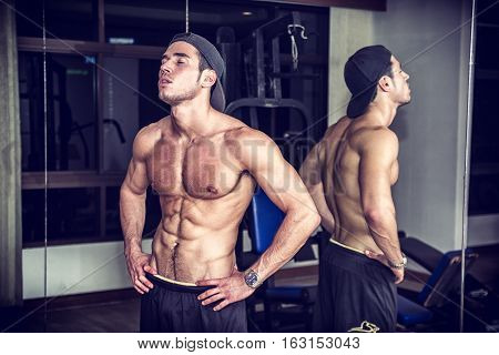 Muscular, shirtless young man resting in gym during workout, showing muscular torso, pecs and abs