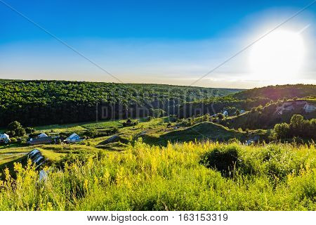 Russian village near the forest on the chalk hills in the light of the evening sun