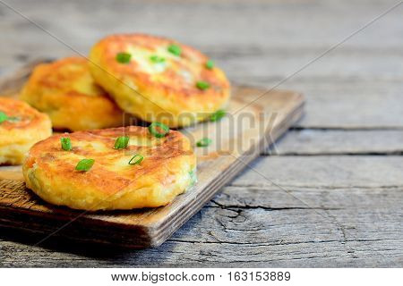 Homemade vegetable cutlets on a wooden board. Healthy cutlets made of potatoes, green peas, carrots and green beans and fried in a pan. Vegetarian dish. Rustic style. Closeup