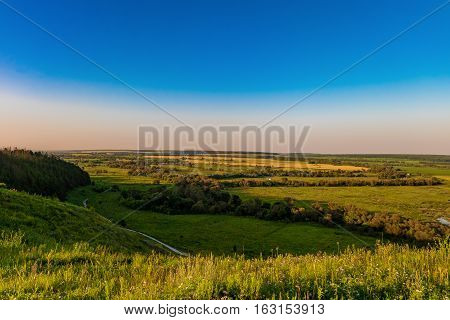 Evening view of the green valley from a high hill