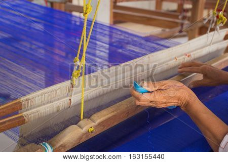 Hands of an old woman who was arrested instruments inserted thread. The loom by hand which is a craft of weaving silk in Thailand.