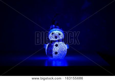 Toy snowman wearing a hat and scarf with blue backlight