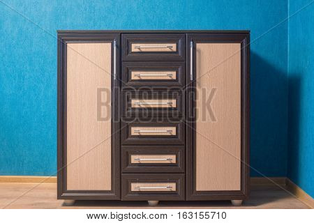 The brown dresser with beige inserts is photographed in an interior against the background of a blue wall