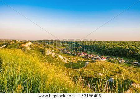 Russian village in a valley between the forest and chalky hills of the ancient archaeological site - Krapivinskaya settlement