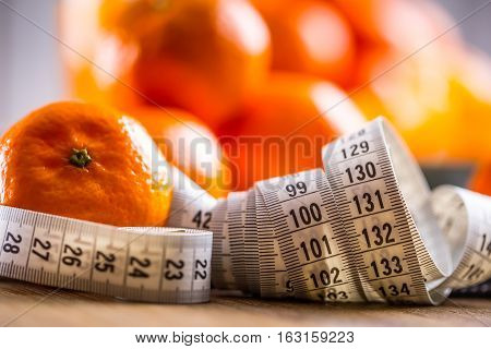 Fresh tropical fruit and measure tape.Tangerines peeled tangerine and tangerine slices on a blue cloth. Mandarine juice.