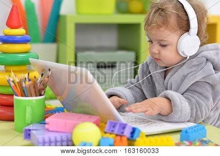 cute little girl listen to music using laptop