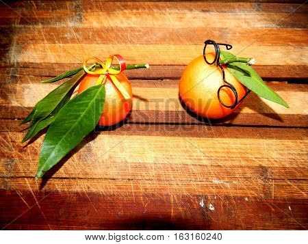 Ripe nectarine orange with glasses and yellow nectarines with a bow with long green leaves lie on the brown wooden kitchen board