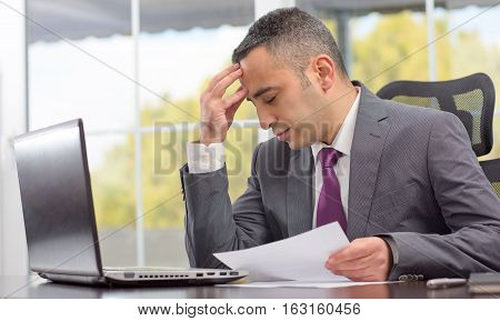 Portrait Of Young Businessman Having Head Ache