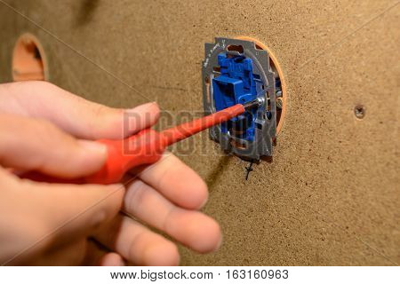 Electrical engineer installing switch at wall of installation - close-up