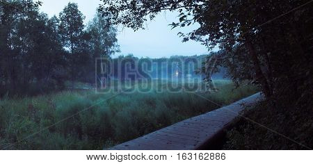 Landscape with small wooden russian-orthodox church fogged on a swamp near holy well