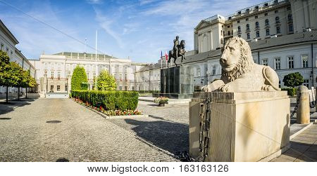 WARSAW POLAND - SEPTEMBER 17: Stone statue of a lion lying in front of the Presidential Palace behind it is a monument to Prince Jozef Poniatowski in Warsaw Poland on September 17 2016