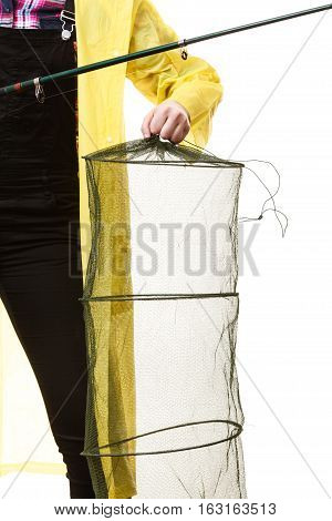 Spinning angling cheerful fisherwoman concept. Woman hand in yellow raincoat holding empty fishing keepnet and fishing rod