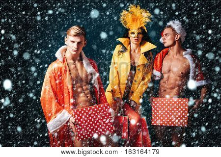 Pretty girl or beautiful woman in golden carnival mask with feathers and sexy lingerie. Handsome muscular men with muscle bodies in red santa suits with Christmas presents on blue wall under snow
