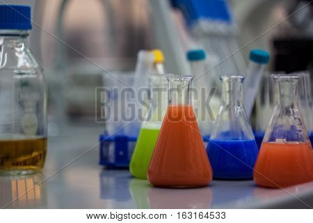Biotechnological Laboratory Equipment For Research. Flasks, Bottles And Pipettes With Colorful Orang