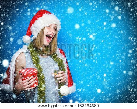 Cheerful pretty girl or cute beautiful woman young female model in santa hat with new year tinsel bauble gift and glass of champagne winks under snow copy space
