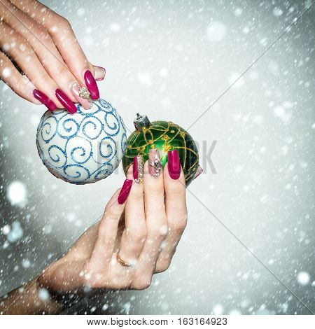 Female hands with fingernail manicure hold beautiful blue and green Christmas baubles with ornament traditional xmas new year decoration balls under snow and snowflakes isolated on white