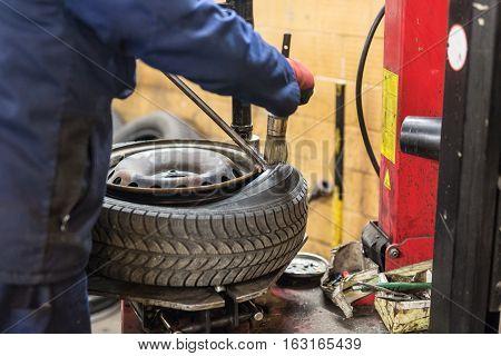 Professional auto mechanic replacing tire on wheel in car repair workshop.