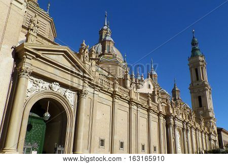 Gorgeous domes and towers of Cathedral-Basilica of Our Lady of the Pillar against vivid blue sky, Zaragoza, Spain