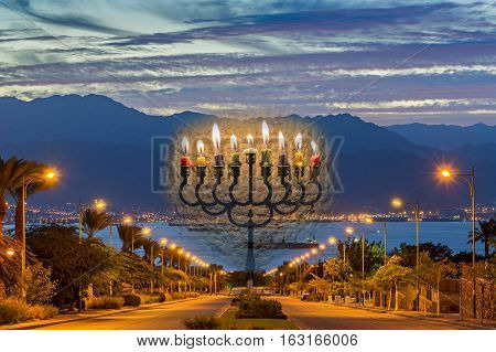 Conceptual image with Jewish menorah as traditional symbol for Hanukkah Holiday. Composite image with menorah and the morning evening at the longest street in Eilat - famous resort city in Israel city