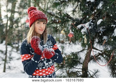 Girl in red cap and mittens standing near the tree. Snow, Christmas and new year mood