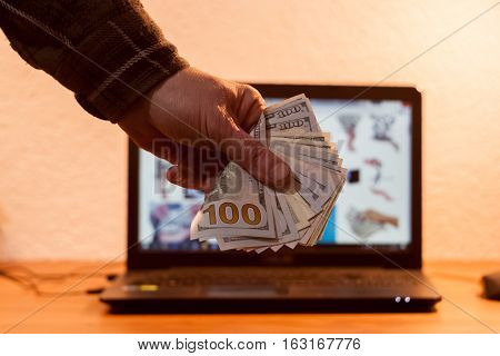 Guy or businessman holding euro money in his hand. Laptop in the background