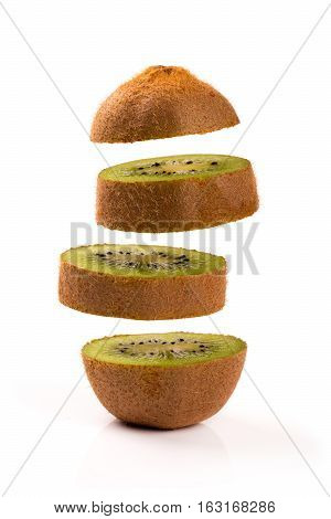 four kiwi slices levitating on white background
