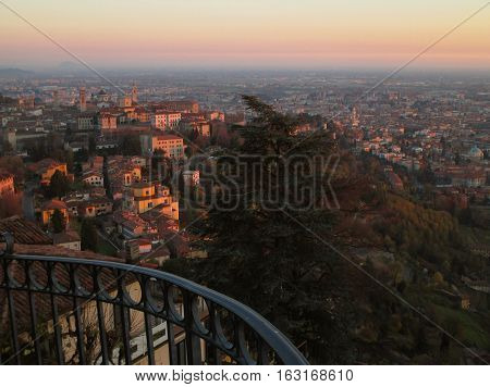 Gradation of sunset afterglow over the lower town, view from the upper town of Bergamo, Northern Italy