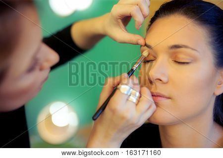 poster of Makeup artist stylist applying eyeshadow on eyelid of woman