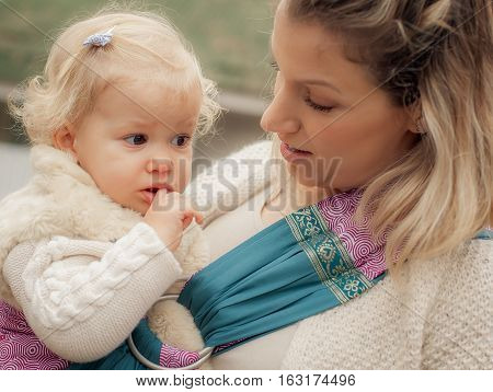 Young Mother Having Her Little Daughter In Baby Carrier Scarf