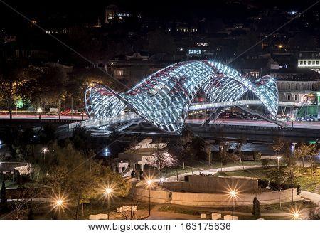 Night view of the Bridge of Peace on the Kura River in Tbilisi, Georgia.
