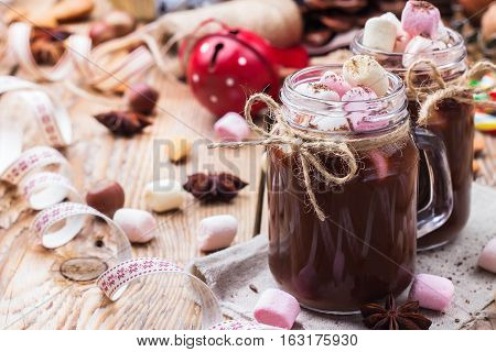 Hot chocolate with marshmallows and spices on rustic christmas table. Selective focus, tasty holidays concept. Drink for fall and winter