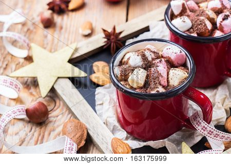 Hot chocolate with marshmallows and spices in red mug on rustic christmas table. Selective focus, tasty holidays concept. Drink for fall and winter