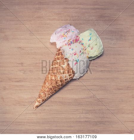Ice-cream cone lying down on a wooden background.